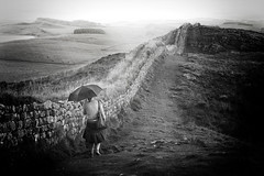 the wall (james_drury) Tags: summer wet rain weather mystery umbrella mono blackwhite day walk story trail northumberland walker national rainy british lonely rambler raining brolly hadrianswall incongruous thegreatoutdoors pouringdown tparain