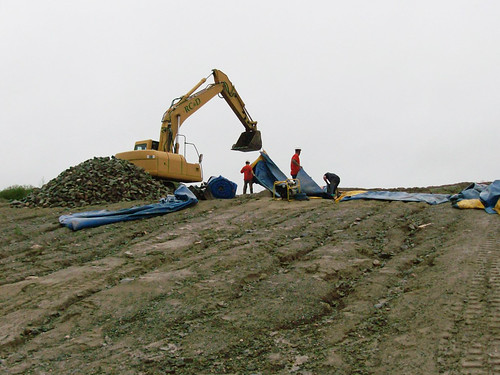 Contractors build an earthen berm to shore up the George H. Nichols Dam as Tropical Storm Irene approaches.