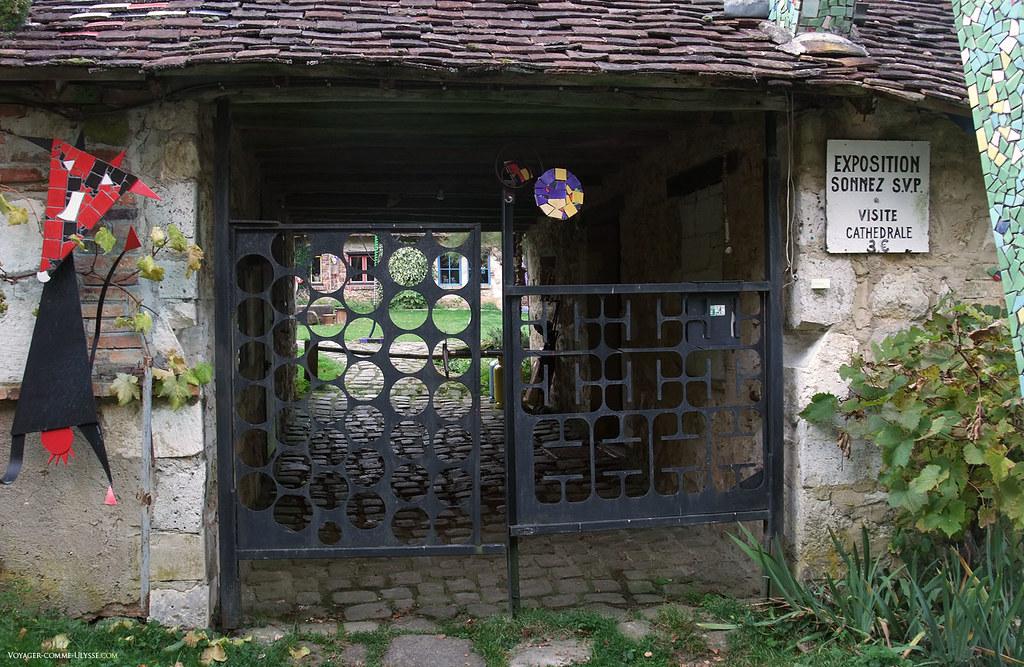 Le portail est lui aussi original, gardé par une vache, sur la gauche. On aperçoit au bout du passage le petit jardin.