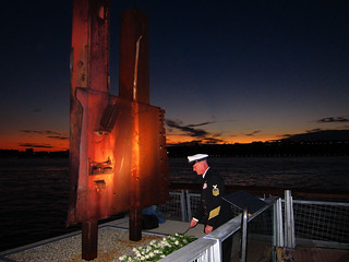 A Sailor lays a white rose at the base of a memorial made from a recovered piece of the World Trade Center at the Intrepid Sea, Air and Space Museum