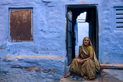 Doorstep, Jodhpur (Marji Lang) Tags: door travel blue portrait people woman india house colour home colors smile composition sitting looking shot geometry femme compo bleu friendly colourful framing blau maison sari couleur doorstep rajasthan jodhpur bluehouse bluecity rajasthani