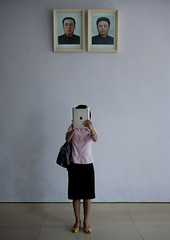 Woman With Ipad In Front Of Portraits Of Kim Il Sung And Kim Jong Il, Panmunjeon, North Korea (Eric Lafforgue) Tags: portrait people woman apple vertical wall asian war asia general korea womenonly kimjongil photograph asie guide coree protection dmz humanbeing northkorea  nationalism modernity dprk coreadelnorte ipad onepersononly realpeople traveldestinations kimilsung northkorean nordkorea  colorpicture 8648 supremeleader  asianethnicity   coreadelnord koreandemilitarizedzone  unrecognizableperson  insidenorthkorea  rpdc  kimjongun coreiadonorte  ipad2