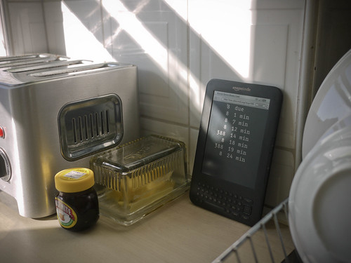 Kindle showing live bus times next to a toaster