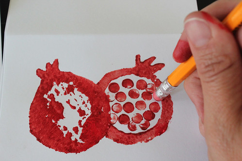 overhead picture of applying painted pencil eraser stamp to paper to make pomegranate on Rosh Hashanah card