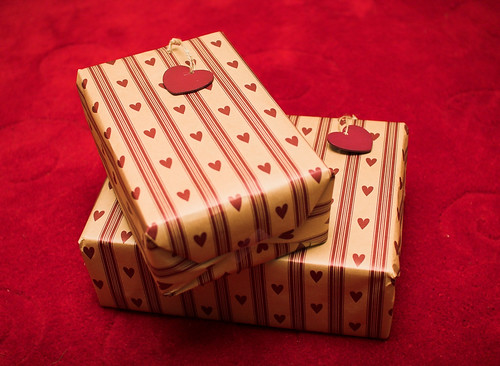 Two rectangular boxes wrapped in red-and-gold heart-patterned wrapping paper, set on a red velvet background