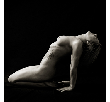 Woman posing in an angular pose for fine art nudes photography.