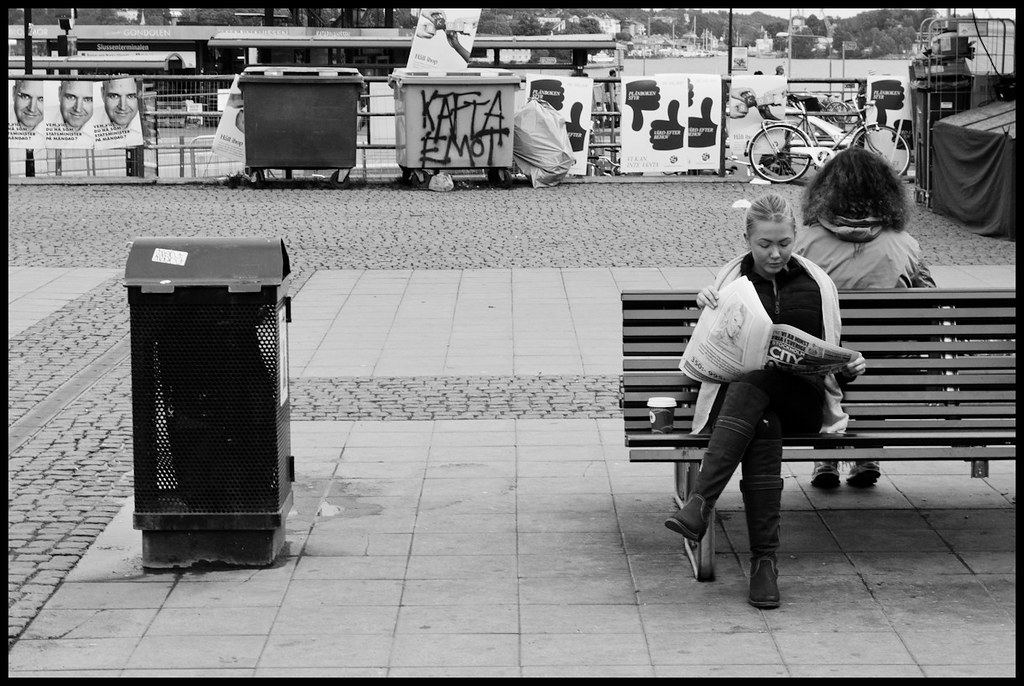 Young woman sitting on bench, reading newspaper, Stockholm, Sweden