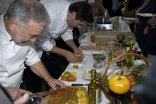 Chef Yves Roquel and his assistant preparing a tomato mix (from the garden) on bruschetta bread with basil (from the garden)