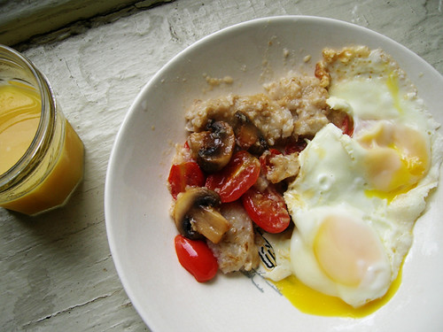 fried eggs and oatmeal with tomatoes and mushrooms