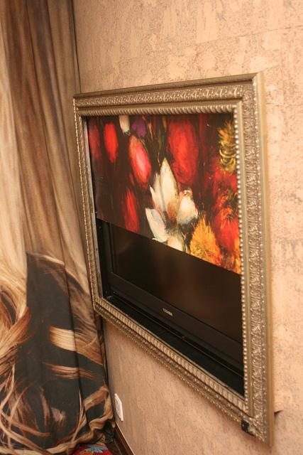 The TV is hidden behind a painting