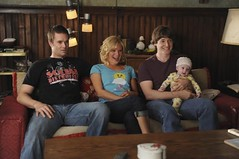 three of the adults on Raising Hope--two white men and a white woman--sit on a couch with a baby