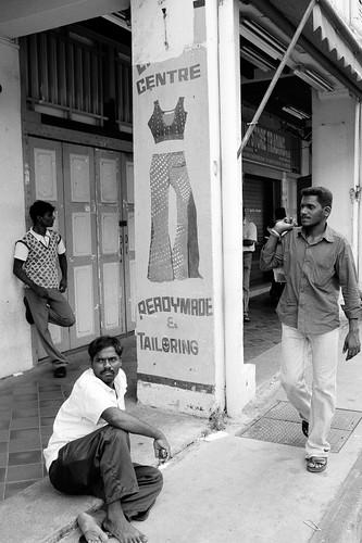 3 men around a pillar. Little India, Singapore