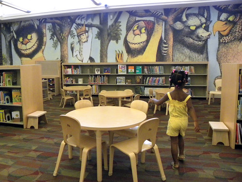 a little girl checks out the Wild Things wall by Enoch Pratt Free Library