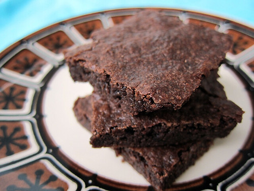 Photo of three thin, fudgy-looking brownies stacked on a small white plate with decorative brown edges.