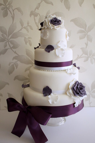 wedding cake with purple ribbon and lace
