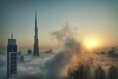 Foggy sunrise in Dubai #1 (momentaryawe.com) Tags: blue orange sun cold fog architecture clouds skyscraper sunrise buildings high warm dubai cloudy uae foggy middleeast aerial tall unitedarabemirates tallest burjdubai intheclouds d300s catalinmarin momentaryawecom burjkhalifa
