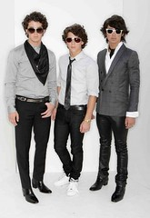 jonas brothers all wearing skinny jeans and sunglasses against a whitish gray backdrop