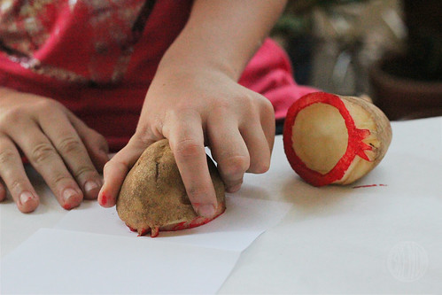 picture of hand applying painted potato stamp to paper for Rosh Hashanah craft