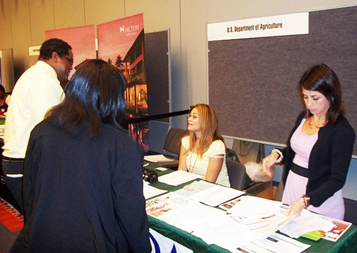 AMS employees at the Congressional Hispanic Caucus Institute career fair. Gilda Villela (left) and Dora Flores (right) hand job fair participants information about AMS.