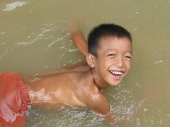 Flooded with Laughter (Khmer Pure Project) Tags: boy sea people water smile asian fun happy kid flooding asia cambodia southeastasia khmer child phnom penh kampuchea