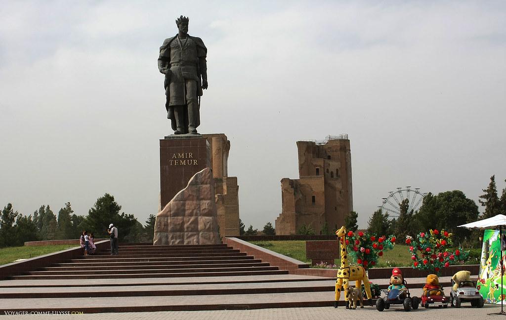 Grande statue d'Amir Timur, face à Ak Sarai, le Palais Blanc. On distingue sur la photo quelques attractions pour amuser les visiteurs et leurs enfants.
