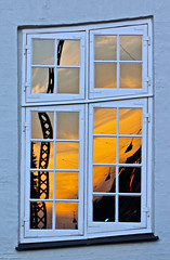 Crooked Copenhagen Window (farastrio) Tags: old sunset reflection window copenhagen delete5 delete2 crane delete6 delete7 fenster save3 delete8 delete3 save7 save8 delete delete4 warped save save2 save9 save4 frame save5 save10 save6 curved wonky kopenhagen fentre crooked tilted askew kbenhavn vindue gluggi orangeandblue vindu copenhague fnster      siluett savedbydeletemeuncensored  silhuet   oppositecolours