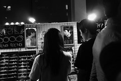 Buying Sunglasses at Night (Paul Jung E) Tags: nightphotography blackandwhite 35mm ambientlight candid streetphotography documentary seoul fujifilm nightlife southkorea highiso hongdae x100 pauljunge