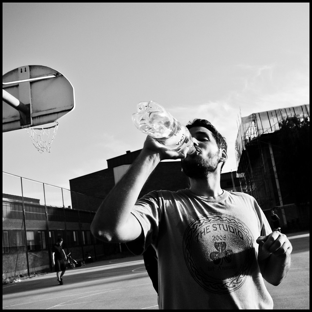 Man drinking water at basketball court, Uppsala, Sweden