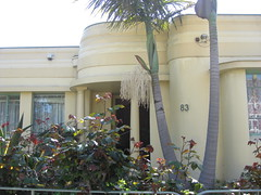 A Streamline Moderne Art Deco Villa - Brunswick (raaen99) Tags: door 1920s windows roses house brick green home window yellow wall architecture century fence pier 1930s wire iron wroughtiron pillar entrance australia melbourne screen brunswick victoria front palm moderne doorway domestic palmtree porch artdeco canopy pillars deco rounded 83 20th gardenwall stucco 30s streamline portico 20s entranceway primrose housenumber twentieth vestibule modernhome eightythree metroland flatroof streamlinemoderne functionalist speedlines featurewall interwar functionalistmoderne stuccoedbrick roundedwall interwararchitecture roundedporch roundedcanopy residencearchitecturebuildingshrubshrubberygardentreeroofroofline
