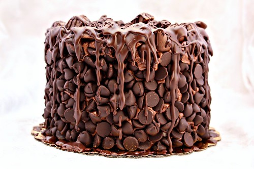 Picture of a multi-tier chocolate cake covered in chocolate chips, candy bars, and drizzled chocolate