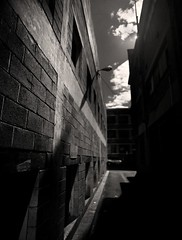 light side of the lane (mugley) Tags: city windows sky urban blackandwhite bw sun blur texture 120 mamiya film car architecture clouds rollei buildings mediumformat prime vanishingpoint alley 645 dof bokeh streetlamp bricks grain perspective angles australia melbourne wideangle victoria scan negative lane epson parked cbd walls gutter asphalt 6x45 narrow r3 bitumen mamiya645 claustrophobic urbanlandscape redfilter enclosed wideopen f35 barreldistortion polariser 25a v700 keystoning mamiya645protl m645 rolleir3 35mmf35sekorn unnamedlane offabeckettst