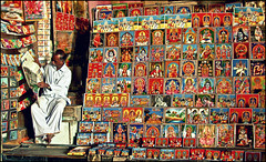 TEMPLE SHOP (manumint-[BUSY]) Tags: morning travel india man shop temple reading newspaper frames bright god vibrant images postcards hindu goddesses tamilnadu rameswaram ramanathaswamytemple