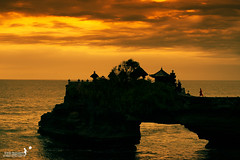 Thousands of candles can be lit from a single candle, and the life of the candle will not be shortened. Happiness never decreases by being shared.. (achew *Bokehmon*) Tags: sunset sea wallpaper bali orange cloud indonesia temple golden waves monk scenary tanahlot