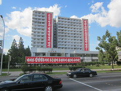 North Korea P'yongyang building emblazoned with propaganda (moreska) Tags: street cars architecture buildings asia propaganda north cityscapes korea scenes slogans pyongyang dprk