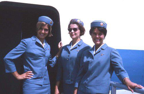 Pan Am flight stewardesses at top of stairs (color)