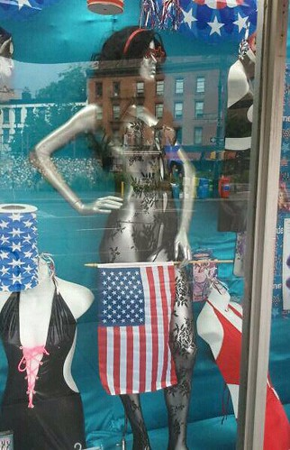 mannequin in window wearing a lace teddy holding an american flag