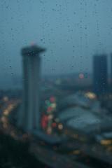 Hesitance.. (MahanMD) Tags: blue sunset red sky rain misty lights flyer singapore shadows darkness citylights illusions marinabay باران غروب hesitance آسمان canon400d دلتنگی تردید روشناییهایشهر کورسو