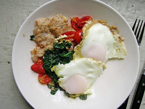 fried eggs and oatmeal with spinach and cherry tomatoes