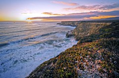 Sunset at the edge... (Joe Ganster) Tags: ocean california ca sunset sea cliff cloud sun seascape water clouds canon boats eos 22 coast boat waves sundown pacific 10 wave down cliffs beam coastal usm bluffs davenport efs 1022mm beams hdr bluff 1022 40d