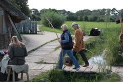 Auf der kleinen Brücke in Haithabu gehen Reinhard Erichsen vom Wikinger Museum und NDR-Reporterin Anke Harnack – WHH 16-09-2011