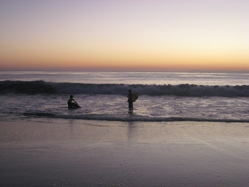 trying out their new boogie boards at sunset
