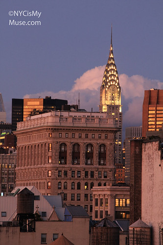 Chrysler Building aglow in gold, back of the Flatiron Building against clouds and a blue twilight sky