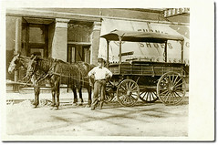 Delivery wagon and driver, Indiana Harbor, Indiana (Hoosier Recollections) Tags: horses people usa signs man men history sepia buildings advertising awning clothing shoes workmen indiana streetscene transportation shops storefronts businesses lakecounty wagons indianaharbor realphoto hoosierrecollections