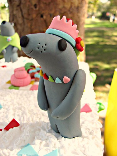 This otter cake decoration looks like it's made of fondant. It's a grey otter, very smooth, with a pink crown on its head, black nose and eyes, and a multi coloured necklace of triangular beads. It sits on a cake with white icing and other colourful decorations.
