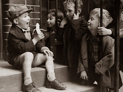 a-little-boy-holding-a-banana-whilst-other-children-gaze-longingly-at-it