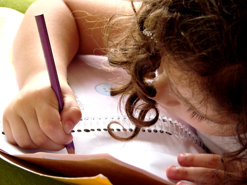 A little girl using a pencil to write on a piece of paper
