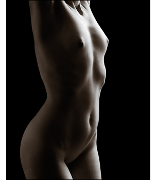 Subtle lighting brings out the contours of woman's abdomen and breasts.
