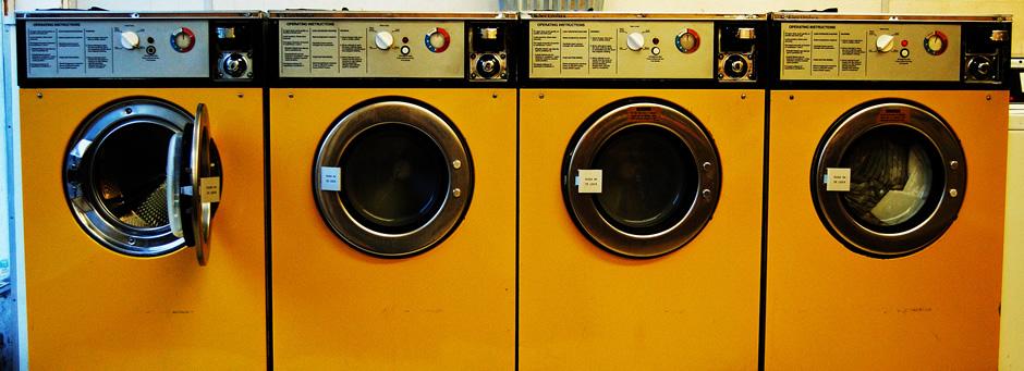 Fotografía de una serie de cuatro lavadoras de color amarillo, una de ellas con la puerta abierta