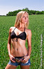 Blonde model with black bikini and ripped demin shorts standing in a field of wheat. Model: Madison MM