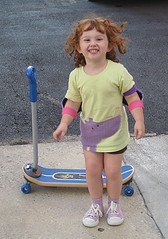 Speck giggling in front of her new skateboard/scooter